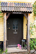 Wellington boots at front door of quaint traditional cottage in Bossington in Exmoor, Somerset, United Kingdom