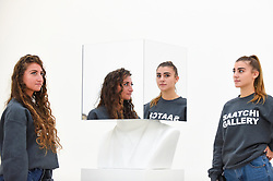 """© Licensed to London News Pictures. 27/09/2018. LONDON, UK. Staff members pose with """"The artist should never contemplate making a work of art that is about something; a successful work of art can only ever be about nothing. The artist's complete negation of intent thus creating a reflective surface into which the critic, curator or collector can gaze and see only himself. Sol LeWitt, Paragraphs on Conceptual Art, 1967"""", 2012, a mirror work by Scott King.   Preview of """"Black Mirror"""", a major new exhibition featuring the work of 26 contemporary artists, at the Saatchi Gallery.  The show explores art's role in social satire and how political uncertainty has influenced art of recent years and runs 28 September to 13 January 2019.   Photo credit: Stephen Chung/LNP"""