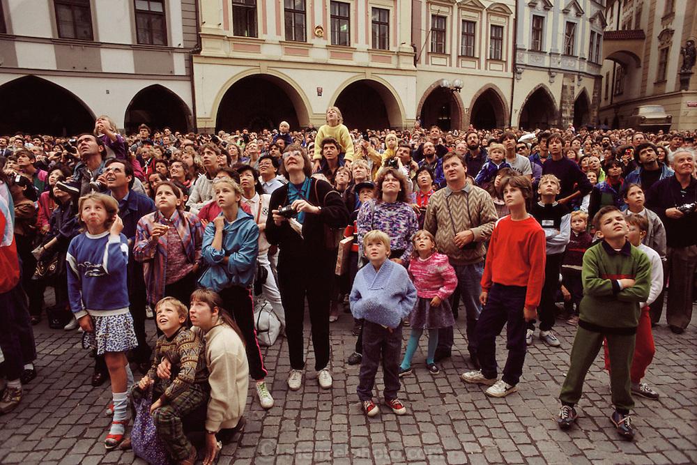 Crowd gathering in Starometske Namesti (old town square) to watch hourly church steeple clock figures. Prague, Czech Republic.