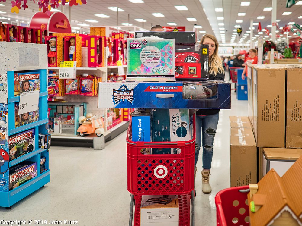 """28 NOVEMBER 2019 - ANKENY, IOWA: A shopper pushes a full cart in the Target store in Ankeny, Iowa. """"Black Friday"""" is the unofficial start of the Christmas holiday shopping season and has traditionally thought to be one of the busiest shopping days of the year. Brick and mortar retailers, like Target, are facing increased pressure from online retailers this year. Many retailers have started opening on Thanksgiving Day. Target stores across the country opened at 5PM on Thanksgiving to attract shoppers with early """"Black Friday"""" specials.    PHOTO BY JACK KURTZ"""