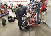 Nederland, Malden, 7-11-2012In de autogarage worden de winterbanden om de velgen gelegd en vervolgens weer aan de auto gezet.Foto: Flip Franssen/Hollandse Hoogte