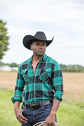 Good looking African American cowboy outdoors on a ranch