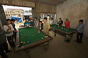 Young men playing pool billiard.