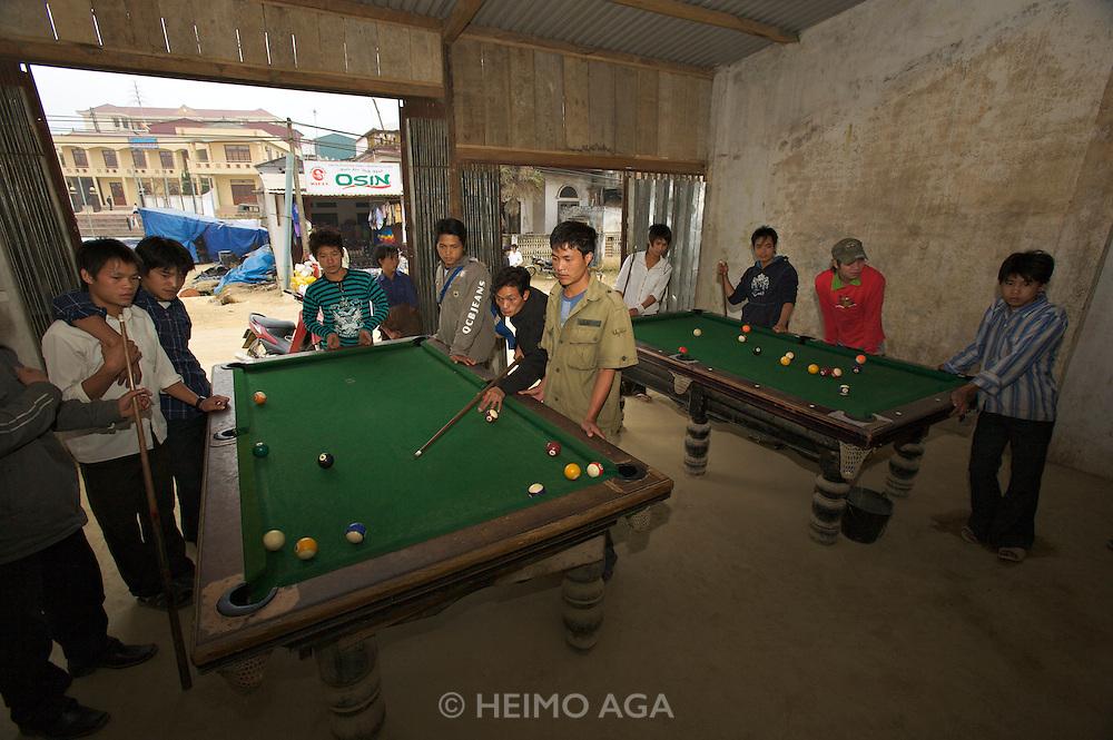 Young men playing pool billiard.