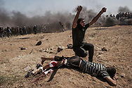 A demonstrator calls for assistance for a wounded Palestinian that waits for evacuation after he has been hit by a sniper bullet in his right leg at the border fence with Israel as mass demonstrations continue on May 14, 2018 in Gaza City, Gaza. Israeli soldiers killed at least 41 Palestinians and wounded over a thousand as the demonstrations coincided with the controversial opening of the U.S. Embassy in Jerusalem. This marks the deadliest day of violence in Gaza since 2014. Gaza's Hamas rulers have vowed that the marches will continue until the decade-old Israeli blockade of the territory is lifted