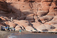 Ship passengers explore beach and red sandstone cliffs of Puerto Gato, Baja, Mexico.