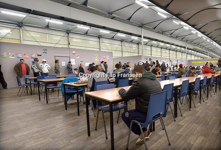Nederland, the Netherlands, Nijmegen, 31-12-2015Niet te gebruiken bij berichtgeving over homofilie.Kamp, tentenkamp Heumensoord, de tijdelijke noodopvang, azc, van het COA. Plaats voor 3000 asielzoekers. In de grote tent waar de eetzaal is staan mensen in de rij te wachten tot ze aan de beurt zijn om hun maaltijd in ontvangst te nemen.FOTO: FLIP FRANSSEN