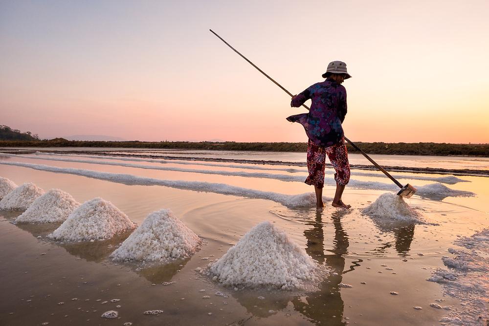 A local women  working in the salt fields at sunset near Kampot, Cambodia. Photo by Lorenz Berna