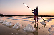 A local women  working in the salt fields at sunset near Kampot, Cambodia. Photo by Lorenz Berna