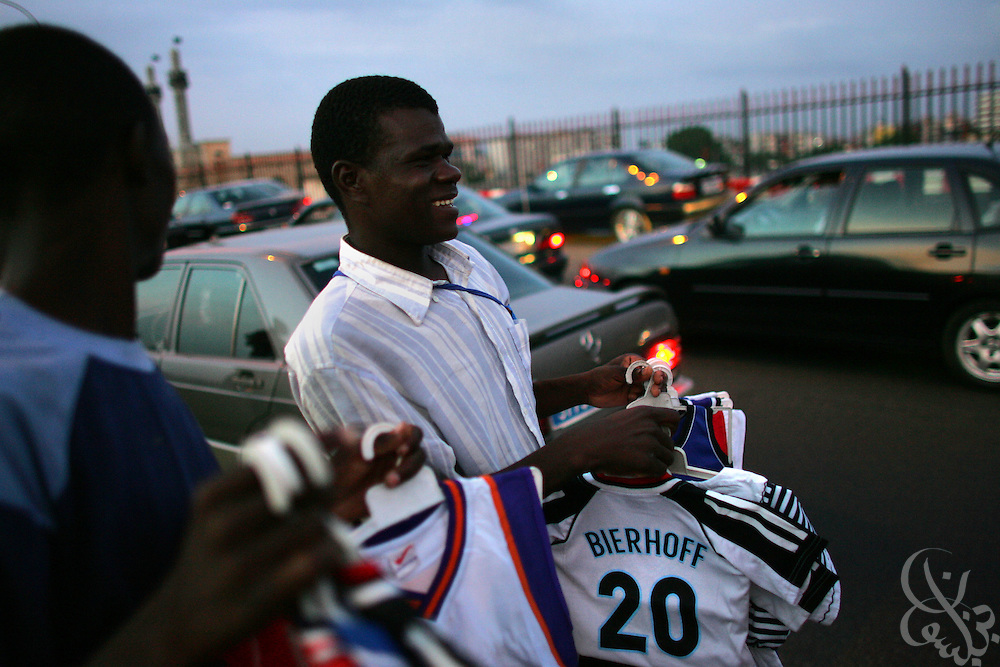Street vendors sell football jerseys (including former German national player Bierhoff) during rush hour in the Plateau district of Abidjan, Côte d'Ivoire February 17,2006. Football is an integral part of the social fabric that makes up Ivorian society.