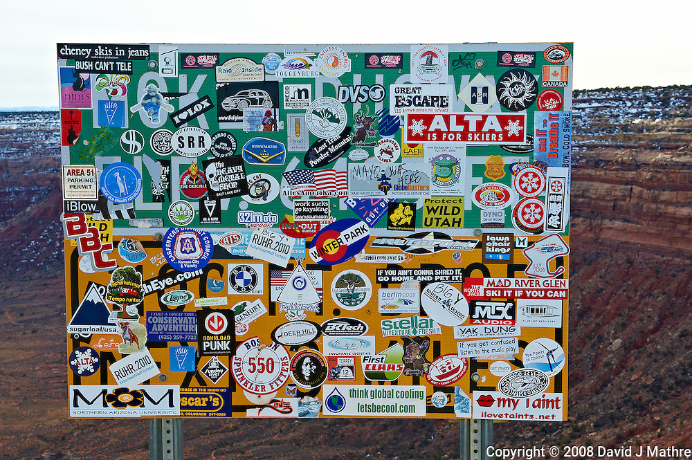 Moki Dugway Road Sign Covered with Bumper Stickers. On top of Moki Dugway on Utah State Route 261, about 6 miles north of Mexican Hat, Utah. Image taken with a Nikon D3 and 24-70 mm f/2.8 lens (ISO 200, 55 mm, f/16, 1/100 sec). Notice the Area 51 Parking Permit on the left side.