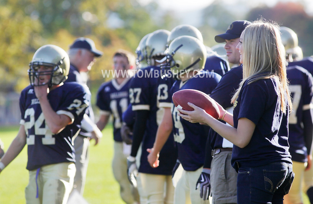 Beacon, New York - A ball girl holds a football on the sideline during a high school football game on Saturday, Oct. 10, 2009.