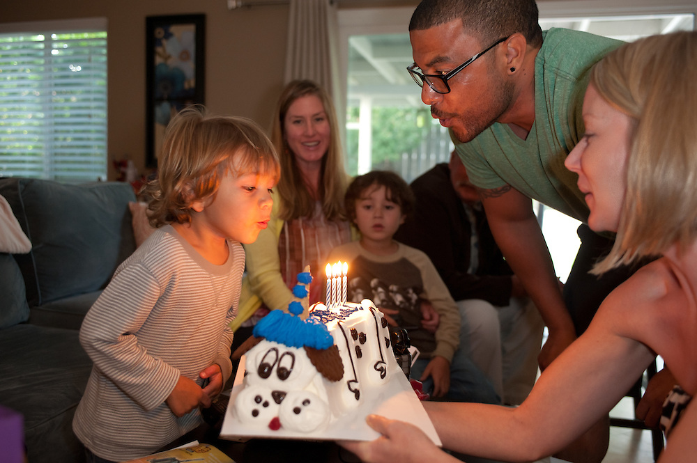 young boy blowing candles on birthday cake, while mother holds the cake, dadpurses lips and aunt and nephew look on