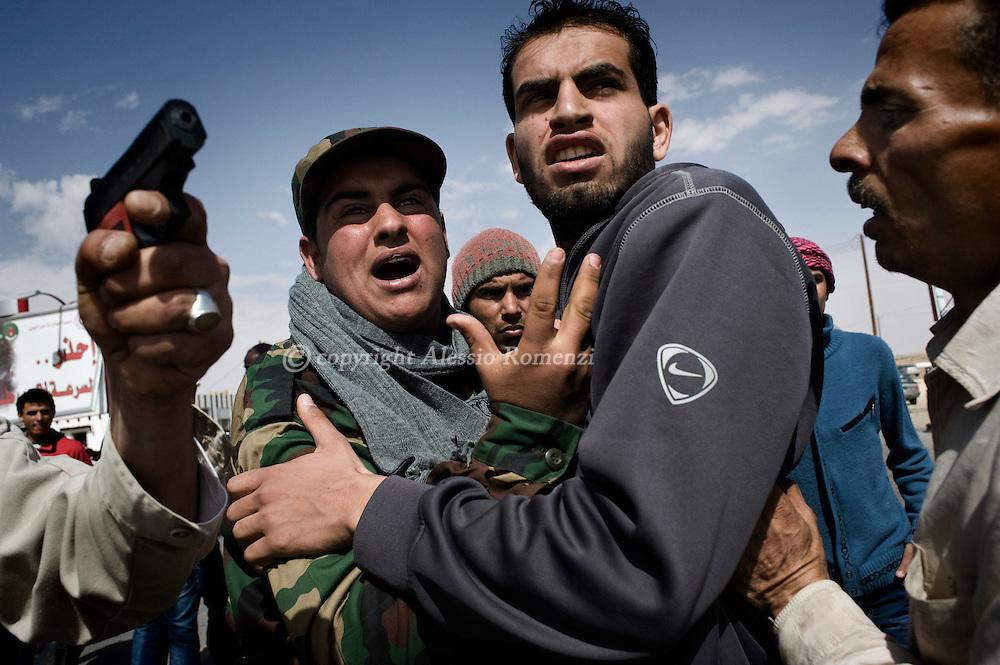 LIBYA, ADJABIYA. Libyan olds a toy gun as rebels argue over an accident of miscomunication, at west gate of Adjabiya, 160 Km south of Benghazi on March 03, 2011. ALESSIO ROMENZI