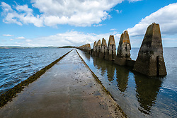 Tidal causeway towards Cramond Island in Edinburgh, Scotland, UK. Concrete structures are wartime anti-submarine defences.
