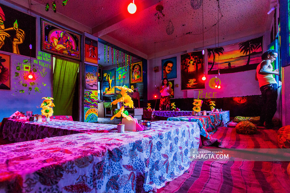 Third Eye Cafe in Kasol, with walls full of glow painting lit with red light