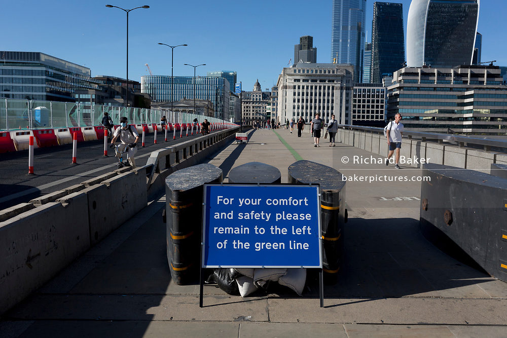 With the UK death toll reaching 38,161, a further 324 victims in the last 24hrs, and the government's pandemic lockdown still in effect, mainly walkers and sightseers now cross at what would normally be rush-hour on London Bridge, which has quickly been converted to a social distancing thoroughfare over the river Thames where pedestrians should keep to the left of a green centreline, on 29th May 2020, in London, England.