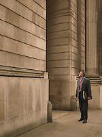 Businessman facing monumental building