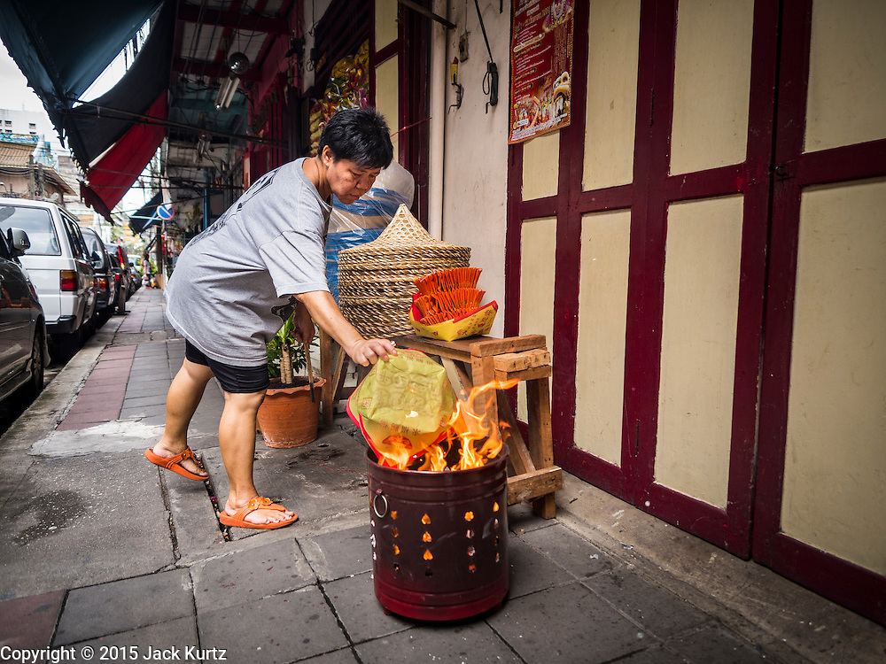 """28 AUGUST 2015 - BANGKOK, THAILAND: A woman burns """"ghost money"""" for her ancestors on Hungry Ghost Day in Bangkok's Chinatown. Mahayana  Buddhists believe that the gates of hell are opened on the full moon of the seventh lunar month of the Chinese calendar, and the spirits of hungry ghosts allowed to roam the earth. These ghosts need food and merit to find their way back to their own. People help by offering food, paper money, candles and flowers, making merit of their own in the process. Hungry Ghost Day is observed in communities with a large ethnic Chinese population, like Bangkok's Chinatown.      PHOTO BY JACK KURTZ"""