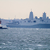 The USS New York built with steal salvaged from the World Trade Center Towers and after having been commissioned in a ceremony on November 8th in New York City leaves New York Harbor.    To the left is the Romer Shoal Lighthouse.
