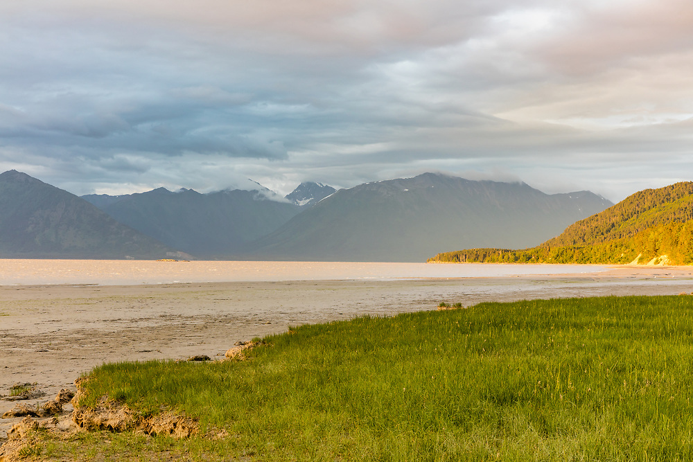 Warm and cool evening light enhance this scenic view of the Chugach Mountains and Turnagain Arm from Hope in Southcentral Alaska. Summer. Evening.