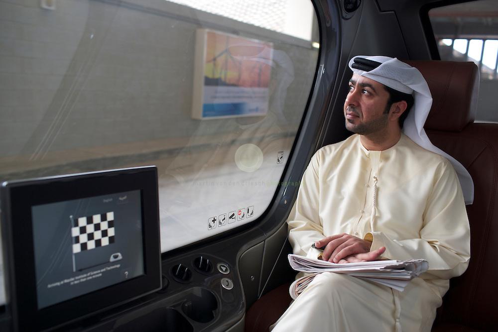 Masdar City. ASIEN, VEREINIGTE ARABISCHE EMIRATE, EMIRAT ABU DHABI, ABU DHABI, 14.04.2011: Fahrgast in einem automatischen PRT-Fahrzeug auf dem Weg zum Masdar Institute. Die Wu?stenstadt Masdar sollte das Silicon Valley fu?r nachhaltige Technologien werden. 2006 rief Scheich Mohammad Bin Zayed al-Nahyan, Kronprinz von Abu Dhabi, das Projekt ins Leben. Die Fertigstellung des Projekts wird sich verzoegern: statt wie geplant 2016 wird die Oekostadt fruehestens 2025 fertig. - Stichworte: Nachhaltigkeit, Masdar, City, Emirat, Vision, Zukunft, Arabien, Stadt, Oekologie, Gruen, Planung, Foster, Architekt, Wueste, Umwelt, Technik, Universitaet, Verkehr, Musterstadt, Verkehrsmittel, Personal-Rapid-Transit, Netz, PRT, 2getthere, Individualverkehr, Fahrzeug, automatisiert, Ziel, Teststrecke, Fahrgast, Araber