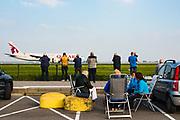 Vliegtuigspotters spotten landende vliegtuigen langs de Polderbaan van Schiphol Airport