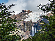 """Multiple waterfalls plunge from Castaño Overo Glacier on Cerro Tronador, an extinct stratovolcano in the southern Andes, near Bariloche, in the Lake District of Argentina, in Patagonia, South America. Seen from the trail to Otto Meiling Refuge. The sound of falling seracs inspired the name Tronador, Spanish for """"Thunderer."""" With an altitude of 3470 m, Tronador stands more than 1000 meters above nearby mountains in the Andean massif, making it a popular climb in Patagonia, South America. Located inside two National Parks, Nahuel Huapi in Argentina and Vicente Pérez Rosales in Chile, Tronador hosts eight glaciers, which are retreating due to warming of the upper troposphere."""
