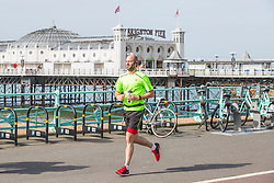 © Licensed to London News Pictures. 13/05/2018. Brighton, UK. Members of the public take advantage of the early morning sunshine to go for a run on the beach in Brighton and Hove as milder weather is hitting the seaside resort. Photo credit: Hugo Michiels/LNP
