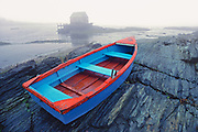 A red and blue rowboat is stranded on a foggy morning at Blue Rocks, Nova Scotia, Canada.