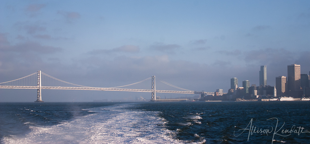 The view of city skyline and Bay Bridge from a ferry leaving San Francisco on a cold and windy day in July.