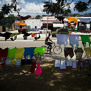 A boy rides a bicycle past women's clothes hanging on lines as they are offered for sale in Santiago, Cuba on Tuesday July 8, 2008.