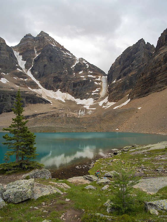 A girl climbs on the rocks, descending toward Oesa Lake with  Glacier Peak and Oesa Glacier (right) in the background, in Yoho National Park, near Field, British Columbia, Canada; MRs available