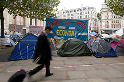 © Licensed to London News Pictures. 27/10/2011. London, UK. An office worker passes the Occupy London demonstrators camp outside St Paul's Cathedral, London today (27/10/2011).  Photo credit: Ben Cawthra/LNP