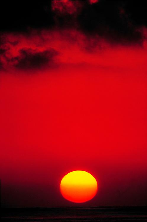 The sun sets into the Pacific Ocean along the California coast.
