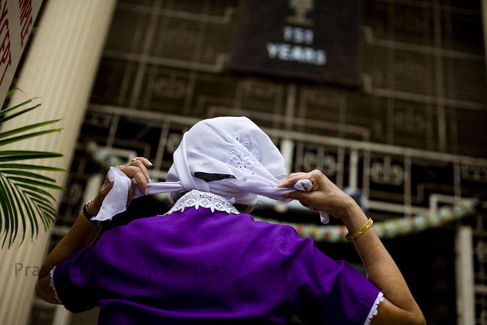A Parsi woman  ties hers scarf as she enters the Kappawala Agiary, or Fire Temple, on Navroze, the Parsi new year, in Mumbai, India, Tuesday, Aug. 19, 2008. Parsis, also known as Zoroastrians, worship fire and are followers of the Bronze Age Persian prophet Zarathustra. According to estimates there are only 150,000 Zoroastrians in the world today and more than 80,000 live in India, mostly in Mumbai. Photographer:Prashanth Vishwanathan/Atlas Press