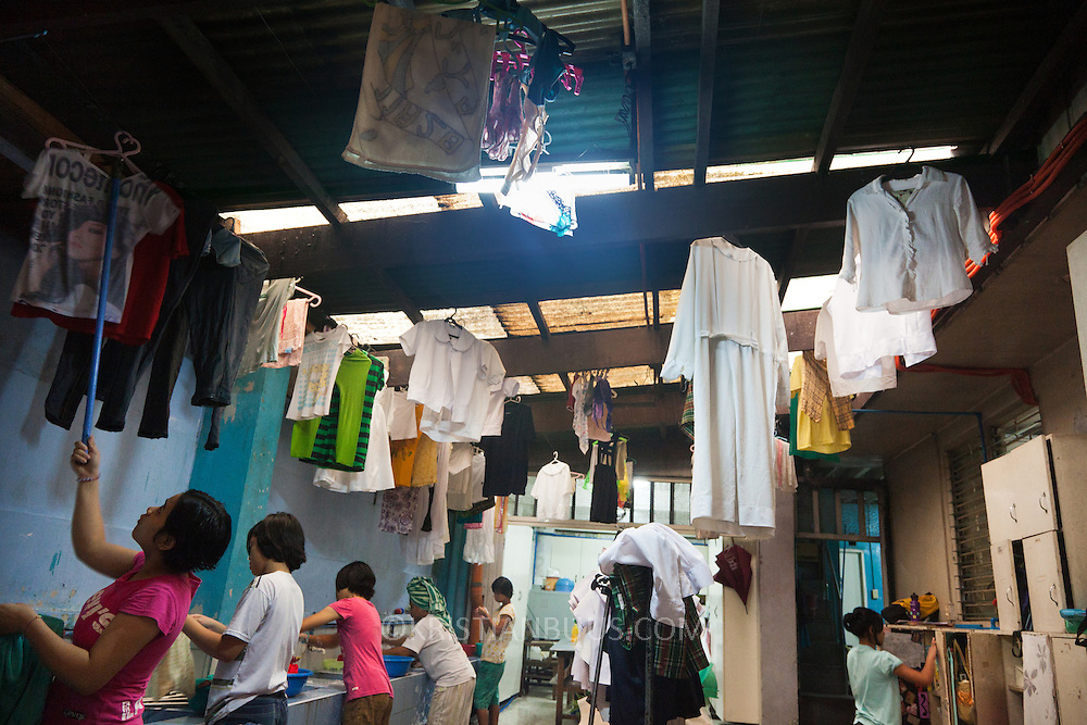 It is laundry day in the center. All the girls are responsible for washing their own clothes and the wash house is busy. Manila, Philippines. Laura Vicu&ntilde;a Foundation, Inc. provides a safe haven, a secure home for girls where they live together with the Salesian Sisters of Don Bosco order. They get the love and care they never have received and psychosocial counseling when needed from qualified psychotherapists. <br />