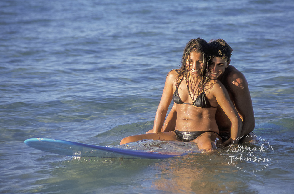 Australia, Queensland, young couple sharing a surfboard.