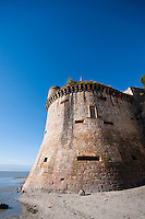 Outer wall of a bastion of Mont-Saint-Michel France from the beach against a brilliant blue sky