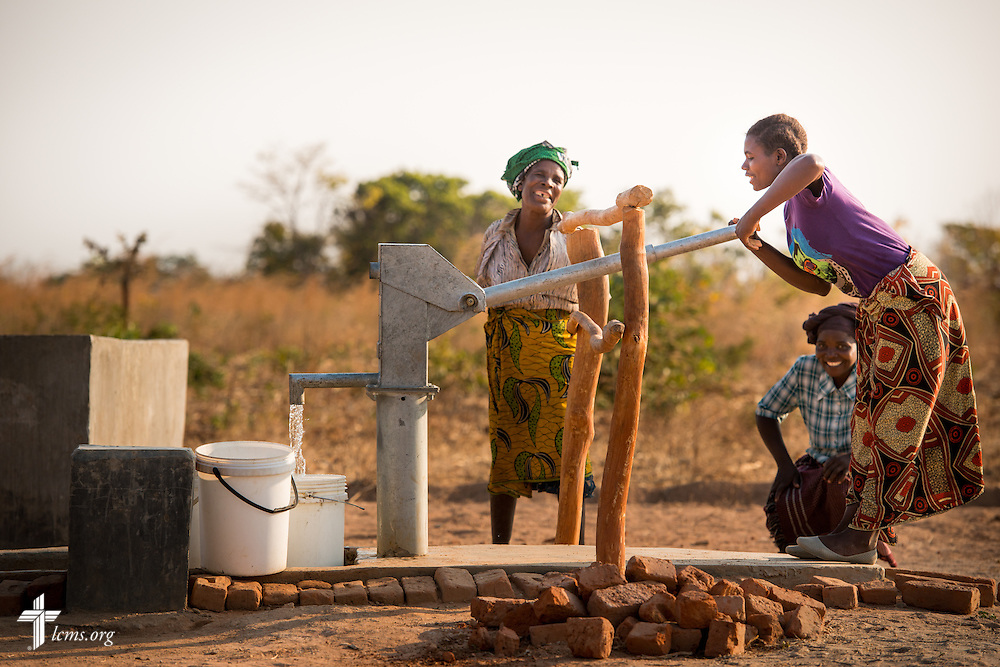 Women pump fresh water from a new LCMS funded well on Saturday, Sept. 26, in Embangweni, Malawi. LCMS Communications/Erik M. Lunsford