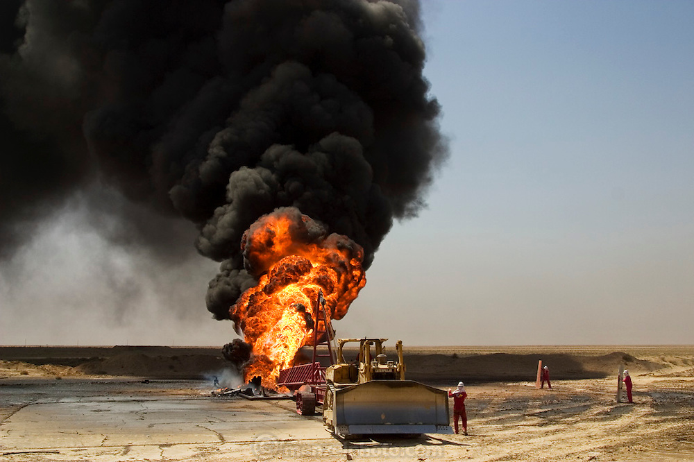 """Firefighters from the Boots and Coots oilwell firefighting company (owned by Halliburton) attempt to kill an oil fire in the Rumaila field by guiding a """"stinger"""" that will pump drilling mud into the damaged well. A """"stinger"""" is a tapered pipe on the end of a long steel boom controlled by a bulldozer. Drilling mud, under high pressure, is pumped through the stinger into the well, stopping the flow of oil and gas. The Rumaila field is one of Iraq's biggest oil fields with five billion barrels in reserve. Many of the wells are 10,000 feet deep and produce huge volumes of oil and gas under tremendous pressure, which makes capping them very difficult and dangerous. Rumaila is also spelled Rumeilah."""