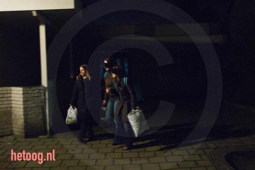 studentes leiden een geblindoekte huisgenoot door de lipperkerkstraat tijdens een ontgroeningsritueel.