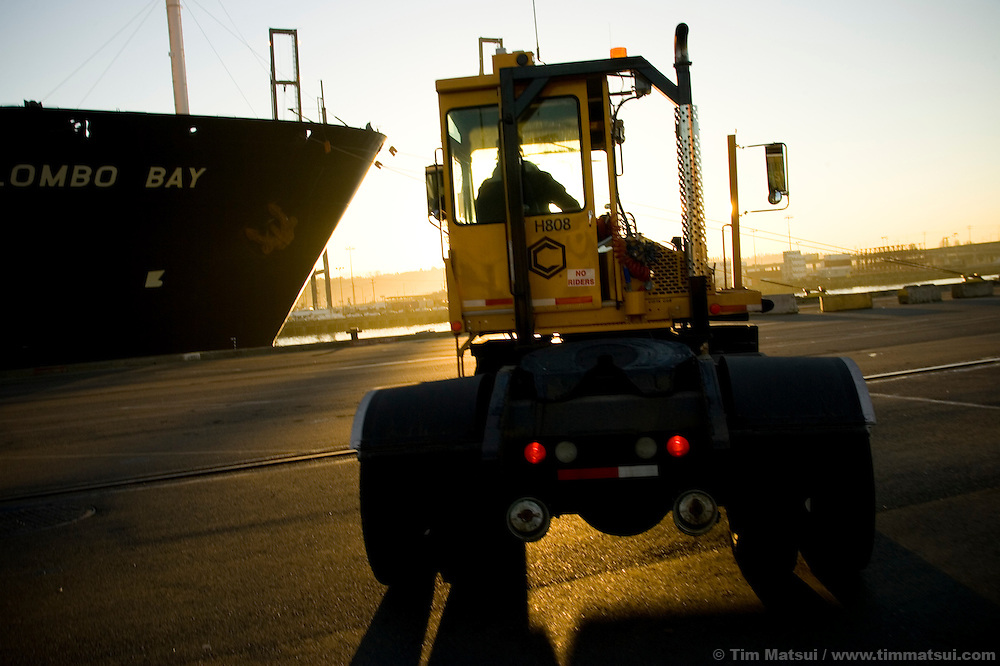 An SSA Marine tractor trailer, called a hustler, moves back and forth between the ship-to-shore crane and the Top Pick lifts which stack the incoming cargo containers at Terminal 18 at the Port of Seattle. The diesel fueled heavy machine will soon be running biodiesel, a more environmentally friendly alternative fuel produced from oilseed crops.