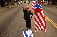 COEUR D ALENE, ID - JULY 17:  A member of the Aryan Nations gives a salute and steps on the Israeli flag during the World Congress Parade held in Coeur d'Alene, Idaho, on Saturday, July 17, 2004. About 40 supporters and members marched in downtown Coeur d'Alene for the Aryan World Congress. (Photo by Jerome Pollos/Getty Images)