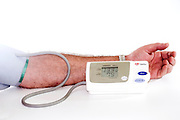 Hypertension - man checking blood pressure and heart rate with a digital blood pressure monitor on white background