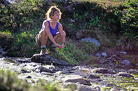 A woman sits by a mountain creek on Whistler Mountain, BC