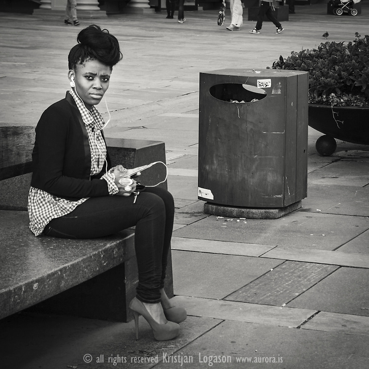 Women wearing blue shoes and jewlery sitting on a bench at torgalmenningen in central Bergen Norway listening to music