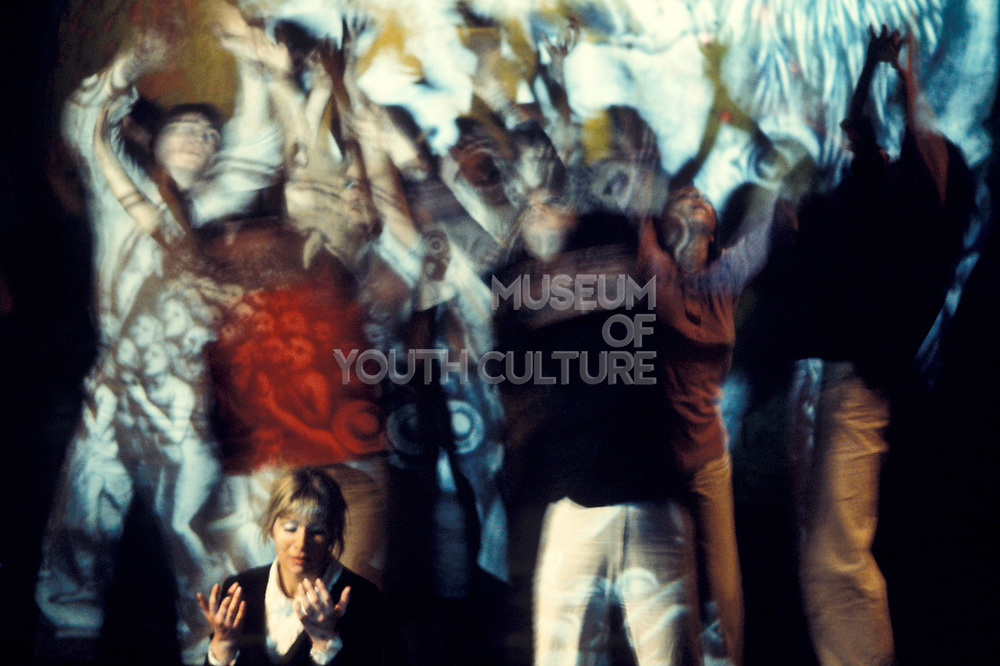 A woman, looking freaked out, on a bad trip, with people dancing behind covered in projections and lights, UFO psychedelic club, London, UK 1970