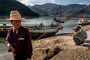 Sand dredgers line the shore of the Lancang (Mekong) river in Simaogangzhen, Yunan, China. The dredged sand is sold locally and to large scale construction sites in nearby major cities such as Kunming and Jinhong.