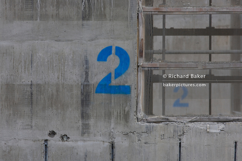 The number 2 stencilled for the second storey of a lift shaft being constructed on a large development project on London Wall in the City of London, the capital's financial district - also known as the Square Mile.